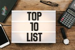 Text topp 10 som är skriftlig i ljus ask för tappningstil på kontorsdesktnolla Arkivbild