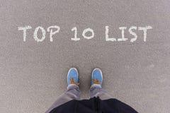Text topp 10 som är skriftlig som text på asfaltjordning, fot och skor på Royaltyfri Foto