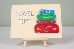 Text travel time, postcard with text and bunch of vintage colored suitcases. Royalty Free Stock Image