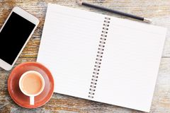 Text 2018 TRENDS on blank paper notebook. Office desk table-Blank paper notebook,smartphone with pencil and cup of coffee on wooden table.View from above.Office Stock Image