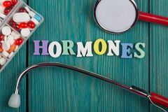 Text u. x22; Hormones& x22; von farbigen hölzernen Buchstaben, von Stethoskop und von Pillen Stockbild