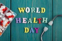 Text u. x22; Weltgesundheit Day& x22; von farbigen hölzernen Buchstaben, von Stethoskop und von Pillen Stockfotos