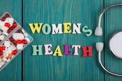 Text u. x22; Women& x27; s-health& x22; von farbigen hölzernen Buchstaben, von Stethoskop und von Pillen Lizenzfreies Stockfoto