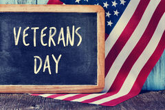 Text veterans day in a chalkboard and the flag of the US. The text veterans day written in a chalkboard and a flag of the United States, on a rustic wooden Royalty Free Stock Images