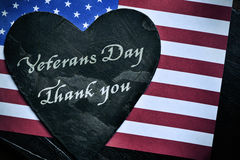 Text veterans day, thank you and the flag of the US. A heart-shaped piece of slate stone with the text veterans day, thank you and the flag of the United States Royalty Free Stock Photo