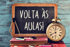 Text volta as aulas, back to school in portuguese. A chalkboard with the text volta as aulas, back to school in portuguese, some old books, an old clock, a Stock Photos