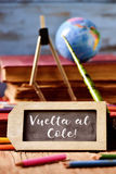 Text vuelta al cole, back to school in spanish. Label-shaped chalkboard with the text vuelta al cole, back to school in spanish, some old books and old Stock Photo