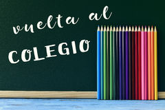 Text vuelta al colegio, back to school in spanish. Written in a chalkboard and some new pencil crayons of different colors put in line, on a blue wooden desk Stock Photos