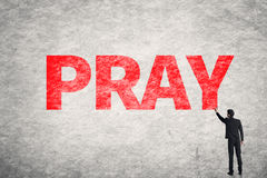 Text on wall, Pray. Asian businessman write text on wall, Pray Royalty Free Stock Photo