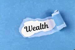 Wealth word. The text Wealth behind ripped blue paper Stock Photography