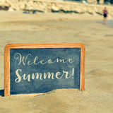 Text welcome summer in a chalkboard, on the sand of a beach Stock Image