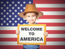 Text welcome to America. Little Funny girl in striped shirt with blackboard. Text welcome to America. On background of American flag Royalty Free Stock Photos