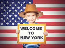 Text welcome to New York. Little Funny girl in striped shirt with blackboard. Text welcome to New York. On background of American flag Royalty Free Stock Photography