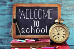 Text welcome to school on a chalkboard. A chalkboard with the text welcome to school, some old books, an old clock, a compass and some pencil crayons of Royalty Free Stock Photos