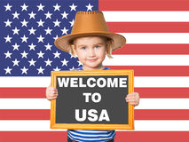 Text WELCOME TO USA. Little Funny girl in striped shirt with blackboard. Text WELCOME TO USA.On background of  American flag Royalty Free Stock Image