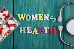 Text & x22;Women& x27;s health& x22; of colored wooden letters, stethoscope and pills. On a blue wooden background royalty free stock photo