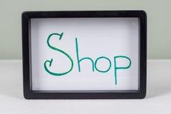 Text word SHOP, black frame, on white table. stock photo
