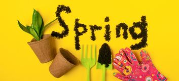The text of the word spring is laid out on a yellow spring background with various garden accessories and tools. stock images