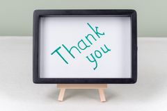 Text word THANK YOU, black frame, on white table. Text word THANK YOU, in black frame, on white table royalty free stock photography