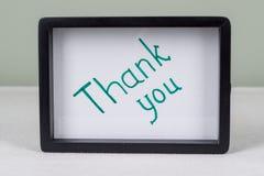 Text word THANK YOU, black frame, on white table. Text word THANK YOU, in black frame, on white table royalty free stock photo