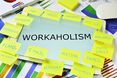The text workaholism in a tablet on an office desk Royalty Free Stock Photo