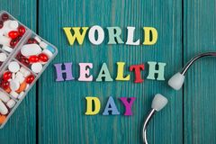 Text & x22;World Health Day& x22; of colored wooden letters, stethoscope and pills. On a blue wooden background Stock Photos