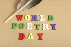 Text WORLD POETRY DAY on wood abc cubes at paper background. Text WORLD POETRY DAY written on wooden cubes. Wooden abc Stock Photo