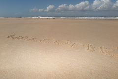 """Text  """"welcome"""" on the beach sand with ocean waves on background Royalty Free Stock Image"""