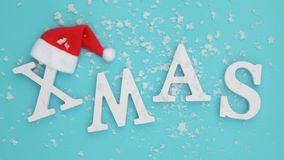 Text Xmas from volume white letters in red Santa hat and falling snow on blue background. Concept Merry christmas. Top. View Flat lay stock footage