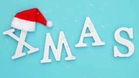 Text Xmas from volume white letters in red Santa hat and falling snow on blue background. Concept Merry christmas. Top. View Flat lay stock video