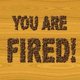 Text You Are Fired coffee on wood texture Royalty Free Stock Images