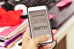 Text you are invited christmas party in a smartphone. Closeup of a young man at his office looking to his smartphone, with the text you are invited christmas Royalty Free Stock Photography