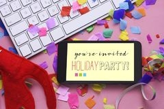 Text you are invited holiday party in a smartphone. A smartphone with the text you are invited holiday party in its screen, on an office desk full of confetti stock photo
