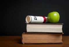 Textböcker med diplomet och äpplet Royaltyfri Foto