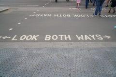 Textblick båda vägar i vitbokstäver på asfalt av gatan i London Arkivfoton