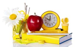 Textbook with a clock and red apple Stock Photography