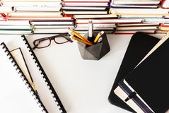 Textbook, laptop, glasses, stack piles of literature, bookshelves in office business background for academic education learning royalty free stock images