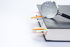 Textbook with multicolor bookmarks and magnifying glass Stock Photography