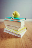 Textbook with yellow apple Stock Photos