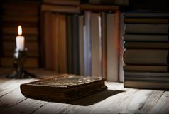 Textbooks and books on a wooden table. Candle light with old book on wooden table in the night. Dark room with out electric light. Copy space Stock Images