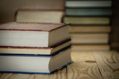 Textbooks and books on a wooden table. Book stack in the library room and blurred bookshelf for business and education background Stock Image