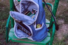 Textbooks and other school supplies to the school in a backpack on a swing stock image