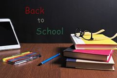 BACK TO SCHOOL. Textbooks, pencil tray, eyes glasses , color pen are on the table in front of a black board Royalty Free Stock Images