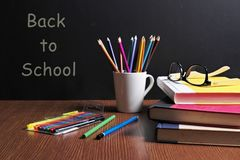 BACK TO SCHOOL. Textbooks, pencil tray, eyes glasses , color pen are on the table in front of a black board Royalty Free Stock Photos