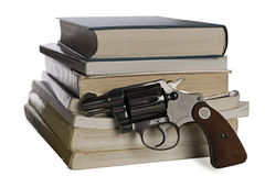 Textbooks and pistol. A .38 caliber pistol stands in front of school textbooks, isolated on white, focus on gun handle Stock Photography