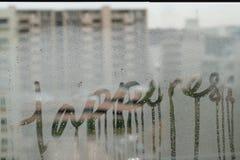 Texte écrit de bonheur sur le verre de fenêtre d'hiver Photographie stock libre de droits