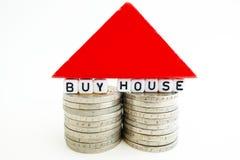 """texte """"Buy de  de house†sur deux piles des pièces de monnaie avec le morceau en bois rouge formant une petite maison Photographie stock"""