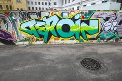 Texte chaotique coloré de graffiti sur la vieille barrière concrète Photos libres de droits