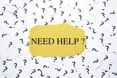 Texte d'aide du besoin sur le papier brun photographie stock