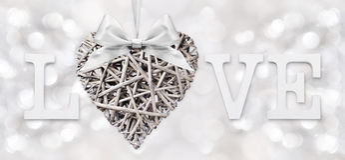 Texte d'amour avec le coeur du bois tissé avec l'arc de ruban sur l'argent Images libres de droits